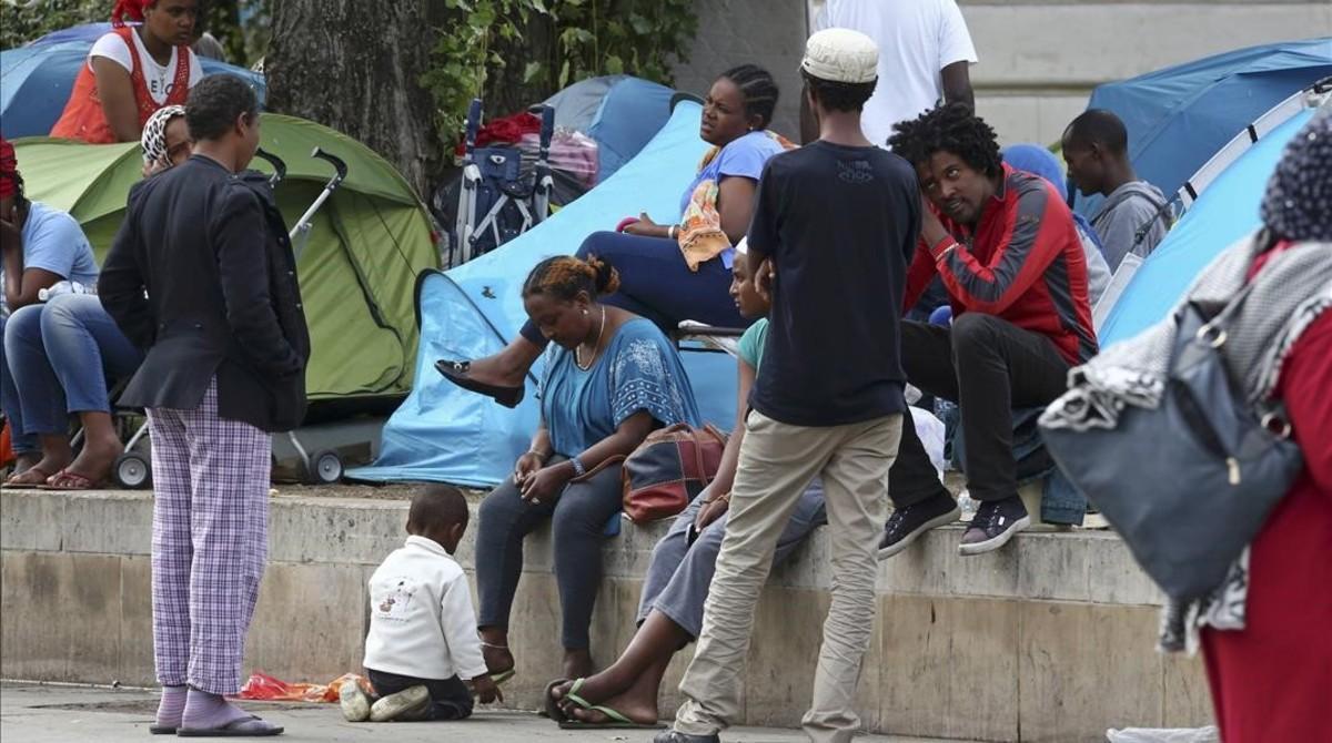 Inmigrantes en un campamento improvisado en una calle del norte de París, este martes.