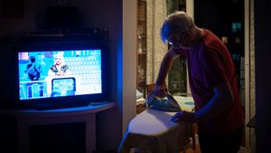 Subida histórica del precio de la luz. Un hombre realiza algunas tareras domésticas frente al televisor