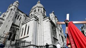 El arzobispo de París, Michel Aupetit, carga con la santa cruz en la ceremonia religiosa de este Viernes Santo frente a la Basílica del Sagrado Corazón de la capital francesa.
