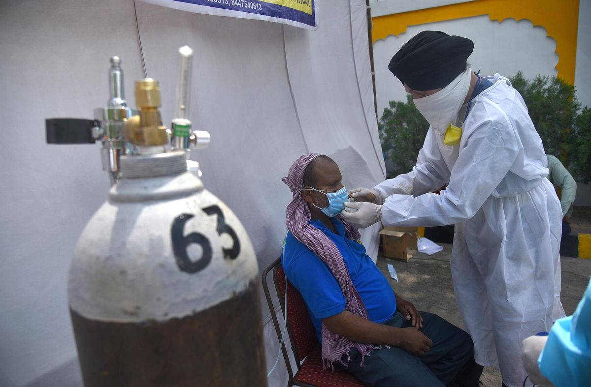 Un sanitario aplica oxígeno a un paciente en Nueva Delhi.