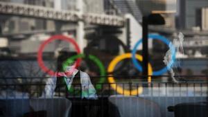 Los aros olímpicos se reflejan en un edificio en Tokio.