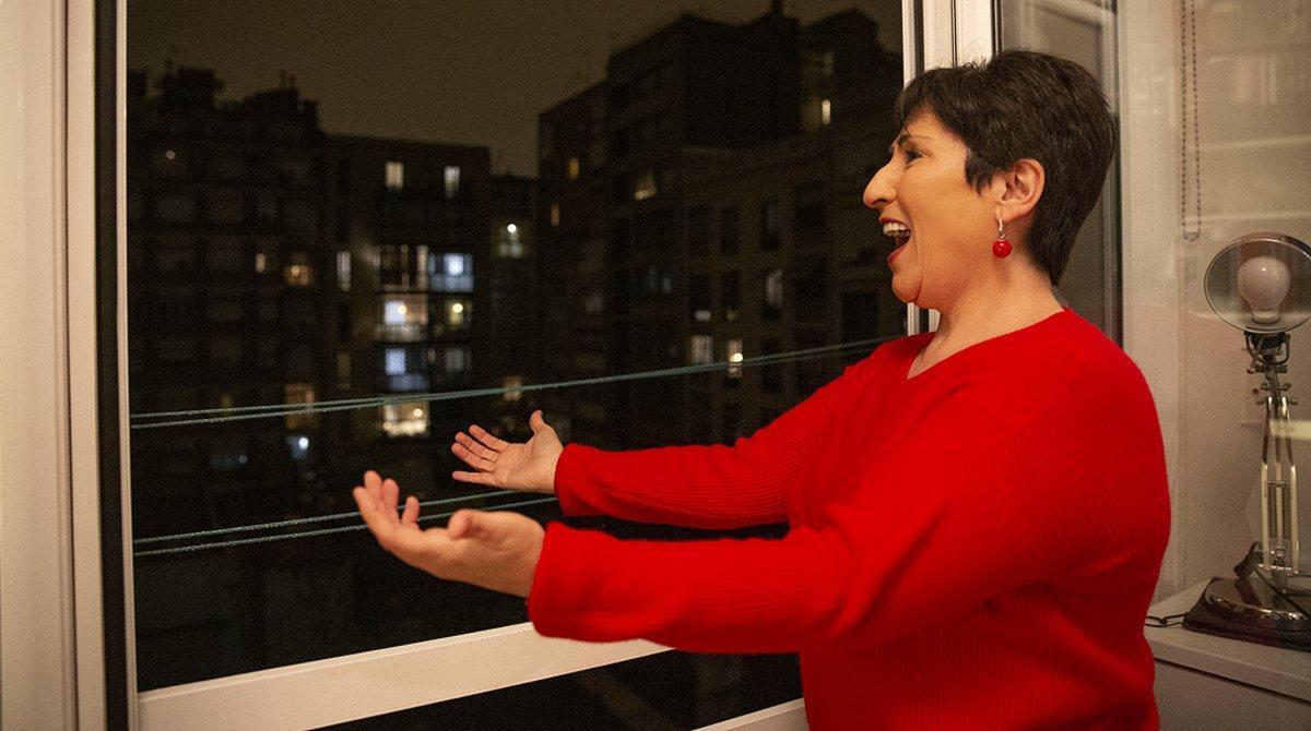 La soprano Begoña Alberdi canta desde su balcón tras los aplausos al personal sanitario, el 16 de marzo, al inicio del confinamiento, en Barcelona.