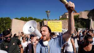 Un hombre usa un megáfono durante la protesta contra el uso de las mascarillas en Madrid