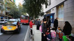 Coches en la entrada de la escuela Dovella, en el Camp de l'Arpa del Clot.