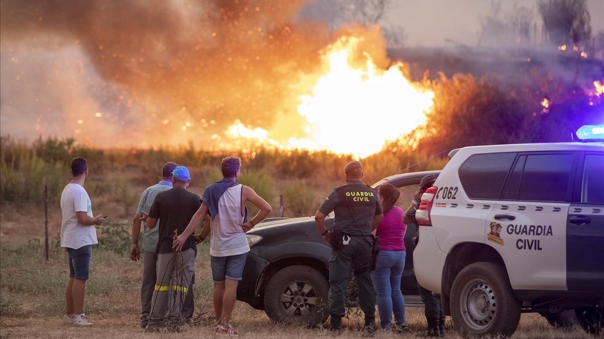 Vecinos observan el incendio forestal declarado en el Paraje Olivargas de Almonaster la Real (Huelva).