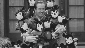 Walt Disney, rodeado de muñecos de su icónico personaje Mickey Mouse.