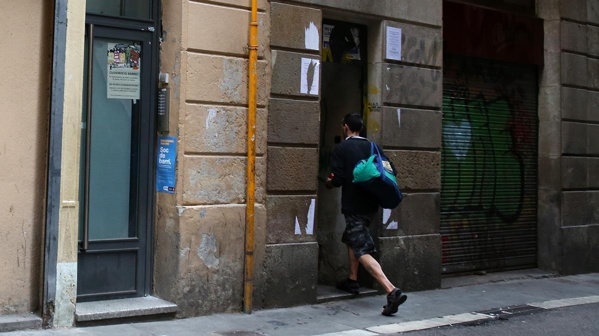 Usuarios entran en el número 22 de la calle En Roig (Raval), uno de los inmuebles más golpeados por los narcopisos.