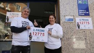 Siscu Flores y Carmen Gordillo, propietarios de la administración agraciada con parte del segundo premio del Gordo, ante la puerta de su negocio, en Santa Perpètua de la Mogoda.