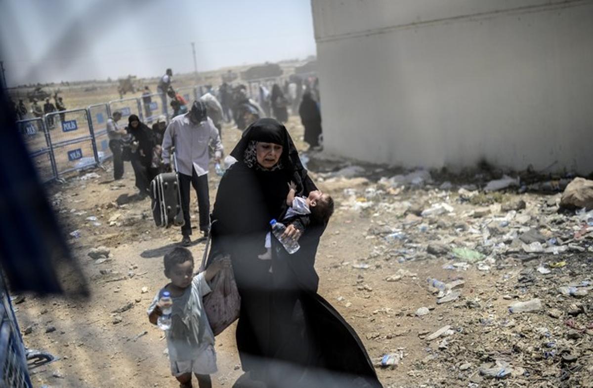 Una refugiada siria, exhausta, pasa con sus hijos a Turquía.