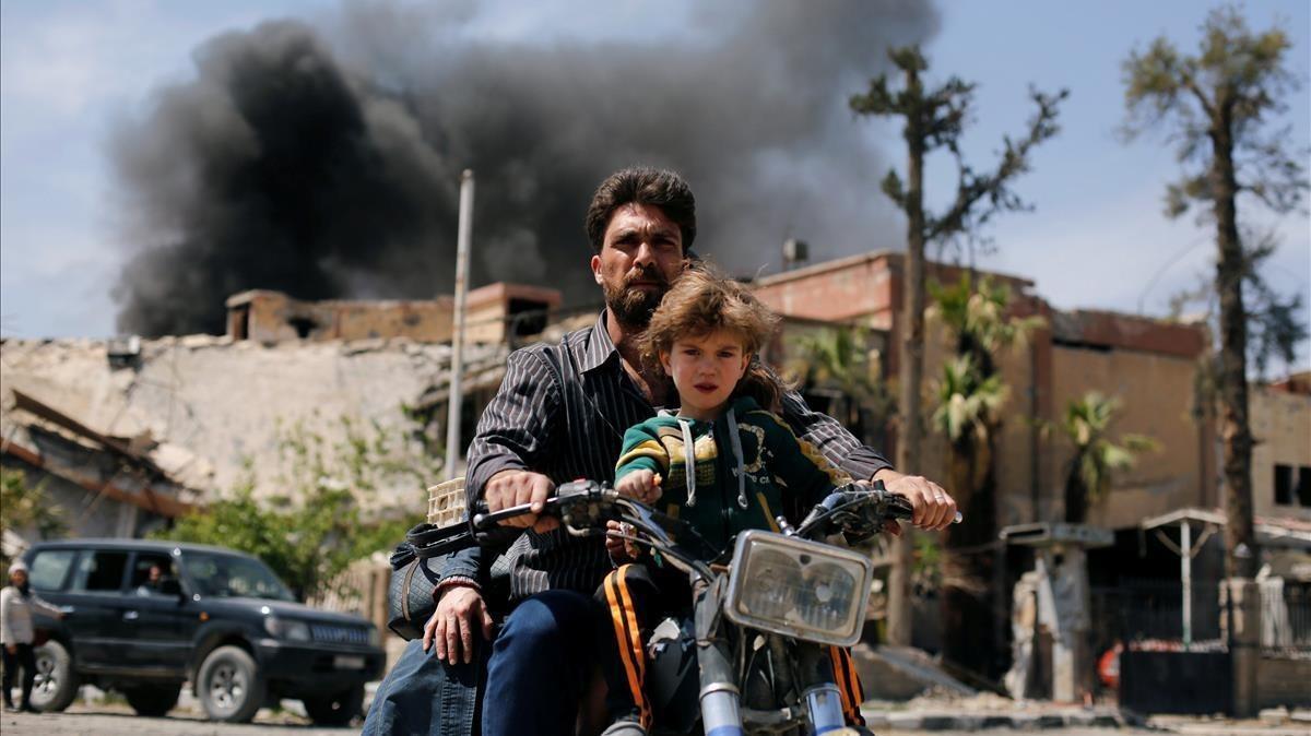 Un hombre con un niño conduce una motocicleta, en Duma.