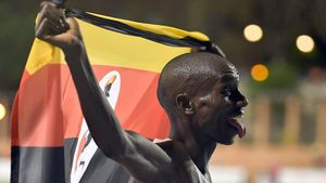Joshua Cheptegei, con la bandera ugandesa en el Estadi del Túria tras batir el récord mundial de 10.000 metros.