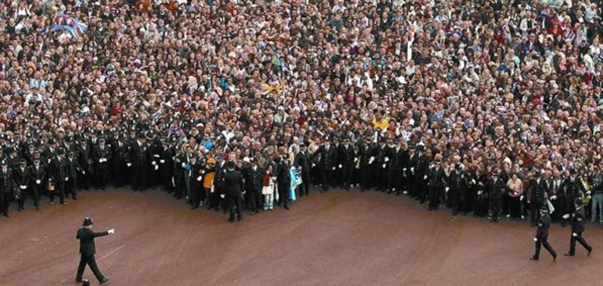 Una multitud en la avenida del Mall espera las indicaciones de la policía para situarse frente al palacio de Buckingham, ayer.