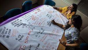 Carla y Xelo, de la asociación Alanna, escriben lemas en una pancarta contra la violencia machista, en 5 de julio en València.