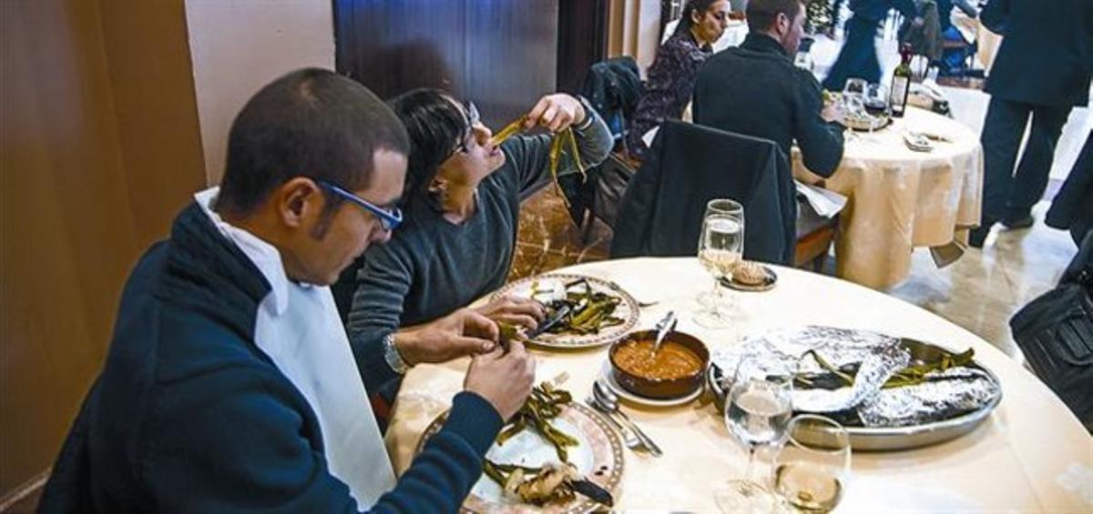 Uns comensals degusten una calçotada en un restaurant, la setmana passada.