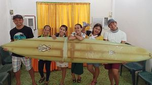 Giovanne Branzuela, a la izquierda, y otros vecinos de la localidad filipina de Sarangani posan con la tabla que ha recorrido más de 8.000 kilómetros perdida.