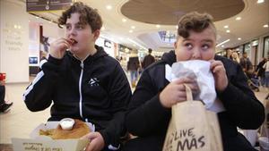 PROBLEMA GRAVE. Una imagen del reportaje, en la que dos niños devoran comida basura.