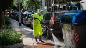 Un trabajador de los servicios de limpieza desinfecta un contenedor en Barcelona
