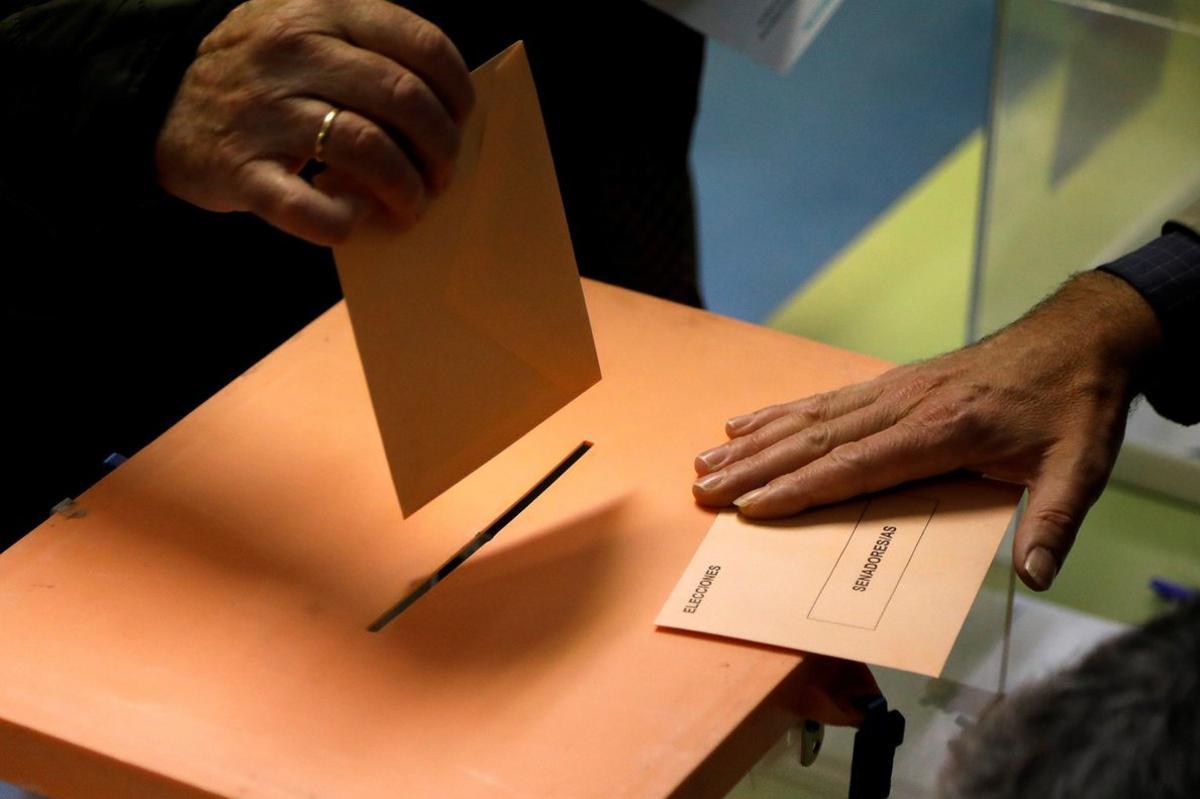 Un ciudadano deposita su voto en una urna.