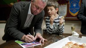 El seleccionador catalán Johan Cruyff firma un autógrafo supervisado por un niño mientras come unos canapés en la presentación de la seleccióncatalana que jugaráel día 30 ante Túnez.