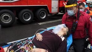 Un bombero auxilia a una mujer herida en el incendio.