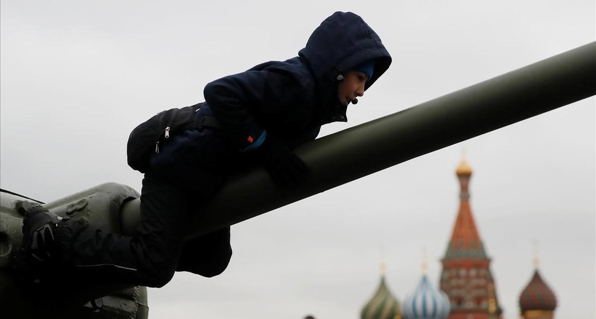 Un niño subido a un tanque de la Segunda Guerra Mundial.