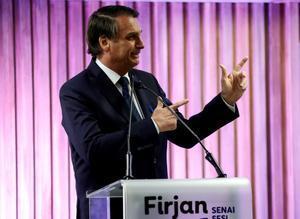 El presidente de Brasil, Jair Bolsonaro, simula disparar un arma.