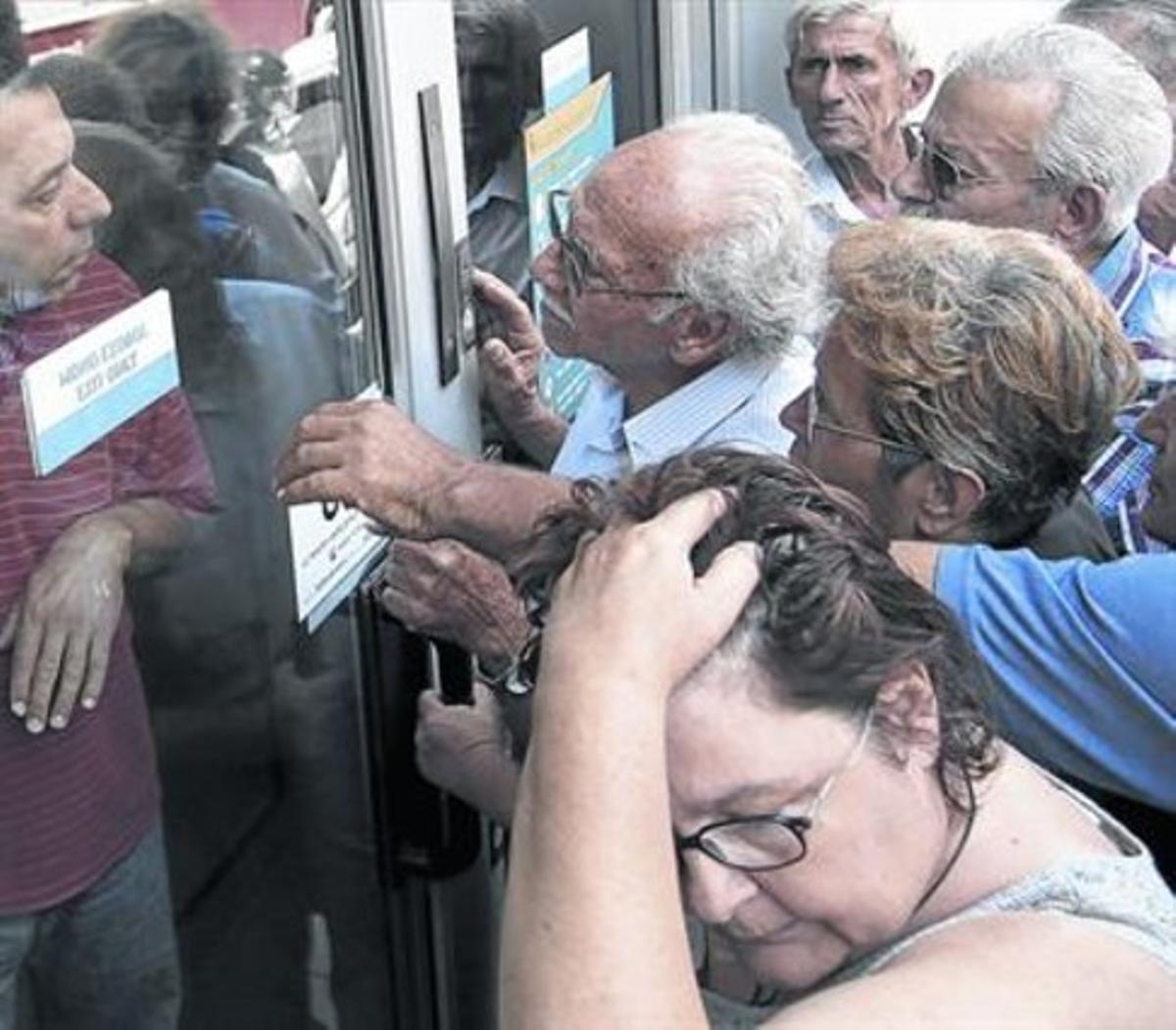 Un grupo de pensionisas espera ante la puerta de un banco en Creta.