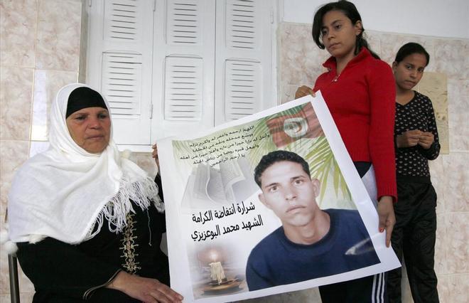 Manoubia Bouazizi sostiene un cartel con la imagen de su hijo junto a sus hijas Samia y Besma en su casa en el distrito de Marsa, en el norte de Túnez. Su hijo Mohamed se prendió fuego en un acto de protesta, hecho que inspiró la Primavera Árabe.