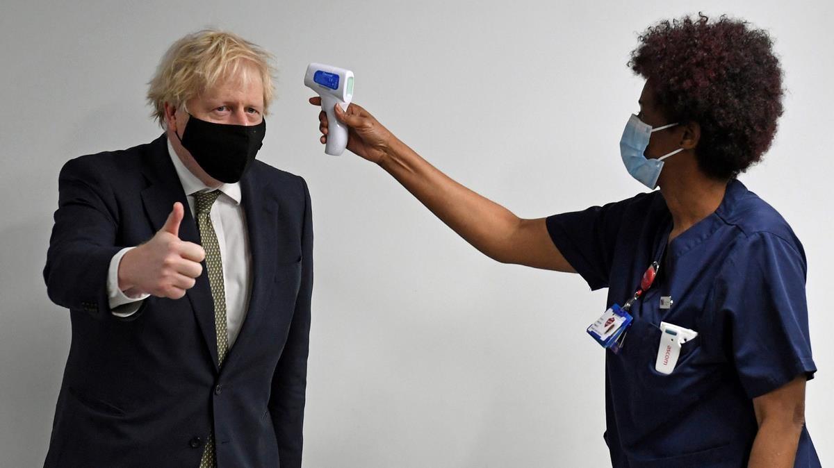 Una mujer toma la temperatura al primer ministro Boris Johnson