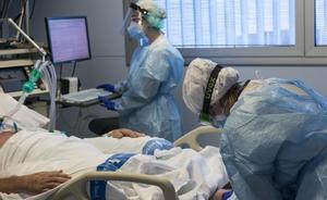 Personal sanitario atiende a un paciente ingresado en la Unidad de Cuidados Intensivos para enfermos de coronavirus del Hospital Josep Trueta de Girona.