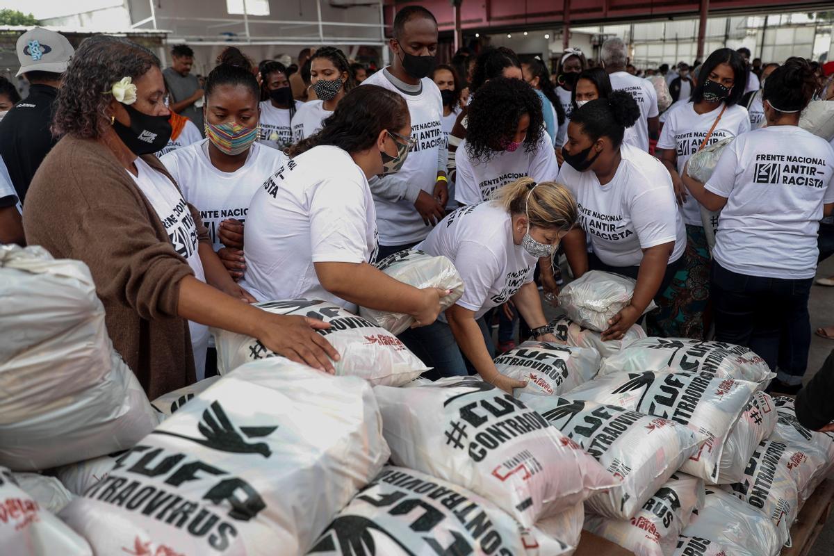 Un grupo de vecinos gestionan la recepción de alimentos donados en una favela.