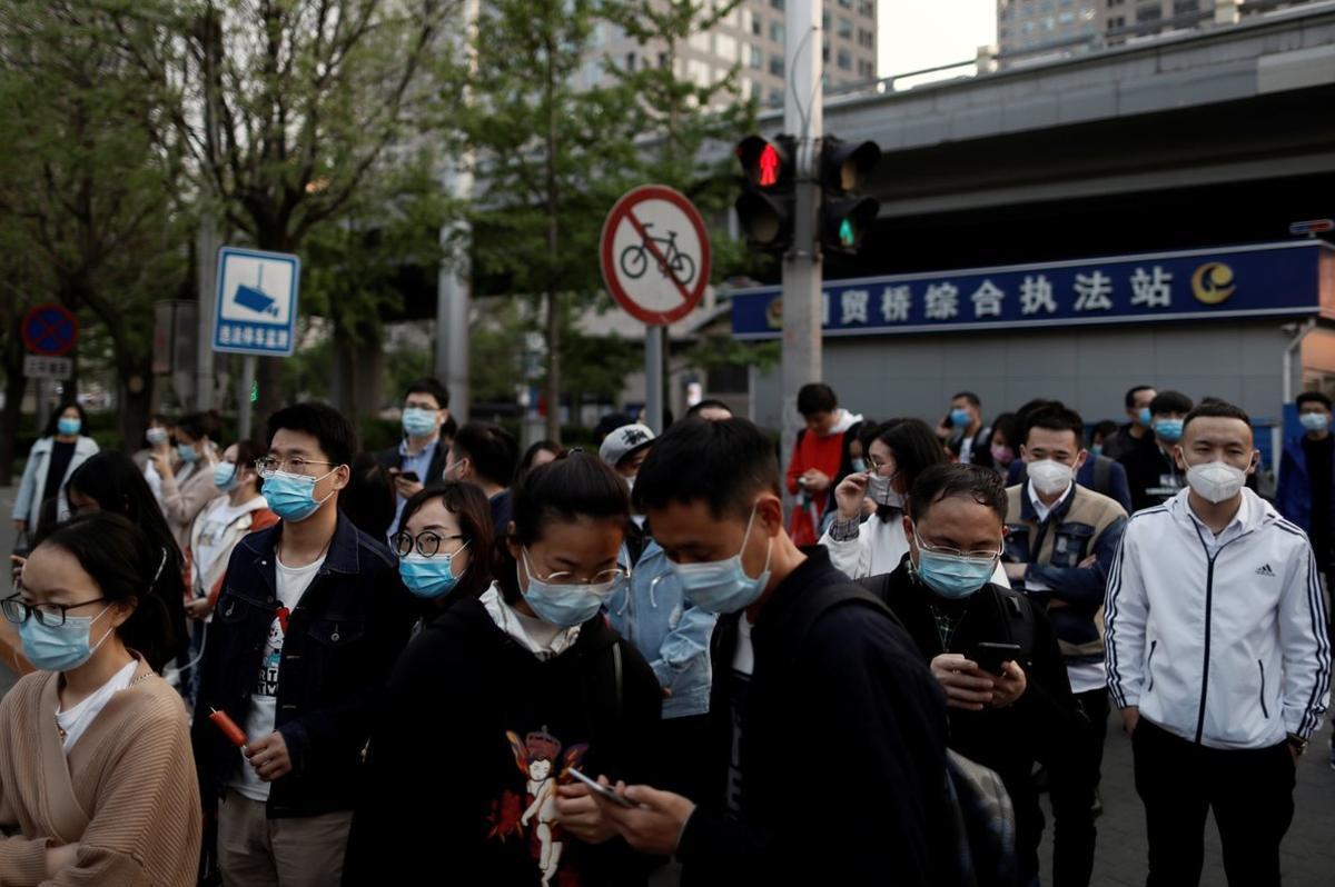 Decenas de trabajadores caminan por el distrito financiero tras concluir su jornada, este viernes en Pekín.