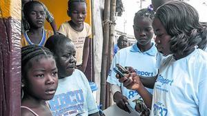 CONTRA EL ÉBOLA.Jóvenes de Liberia leenmensajes contra la epidemia.