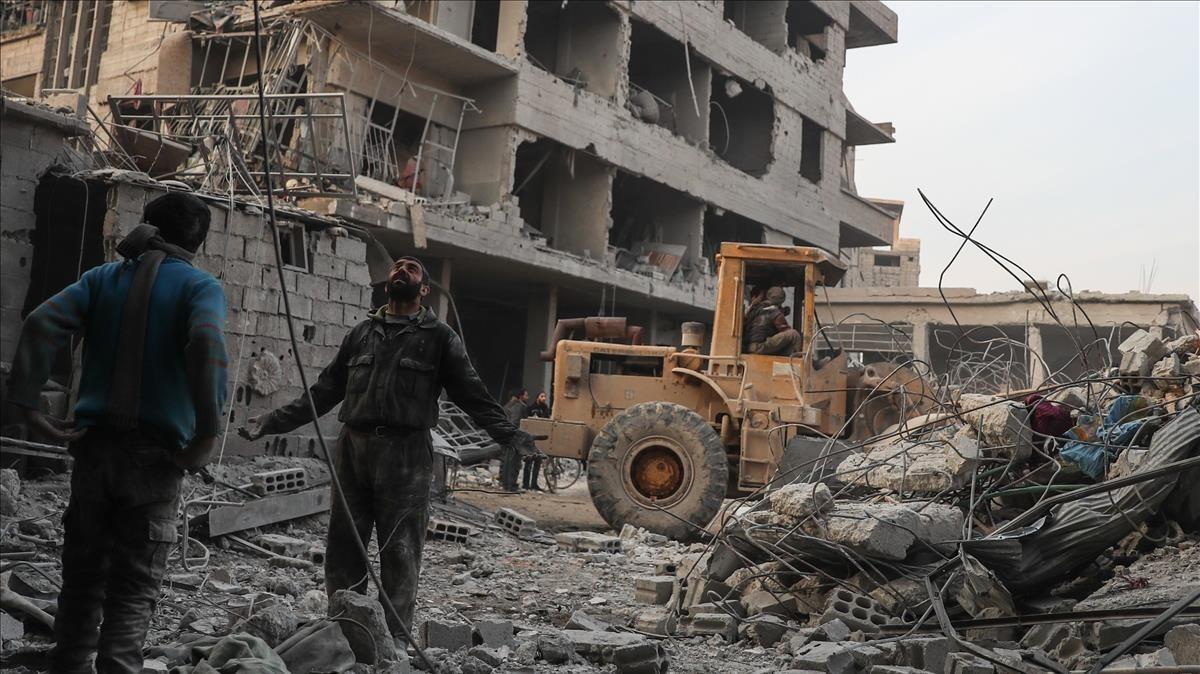 Civiles y voluntarios de la Defensa Civil Siria buscan sobrevivientes tras varios ataques aéreosen la ciudad de Hamoria, en Guta.