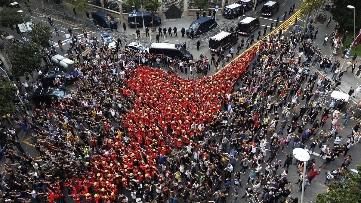 Numerosas personas concentradas ante la delegación del Gobierno en la que han destacado un grupo numeroso de bomberos de Barcelona uniformados que han secundando la jornada de paro.