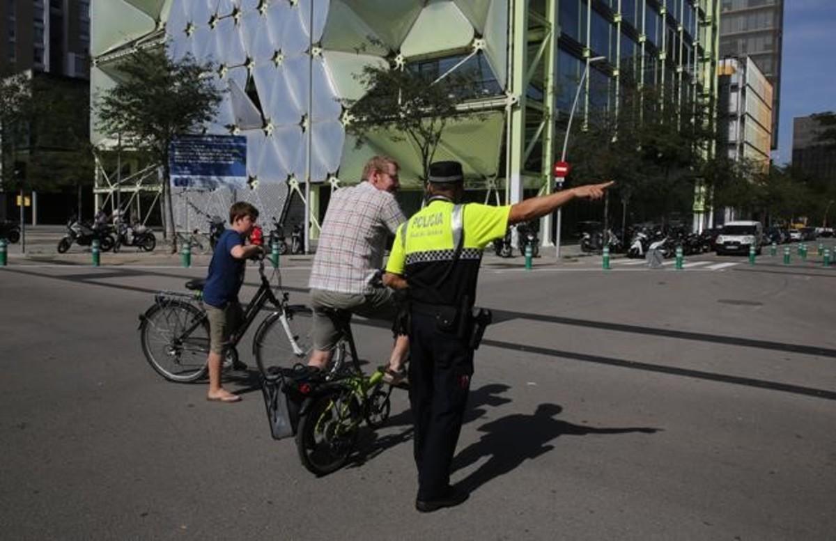 Un policía orienta a un padre y a su hijo, residentes en la zona, sobre la circulación por la supermanzana de Sant Martí.