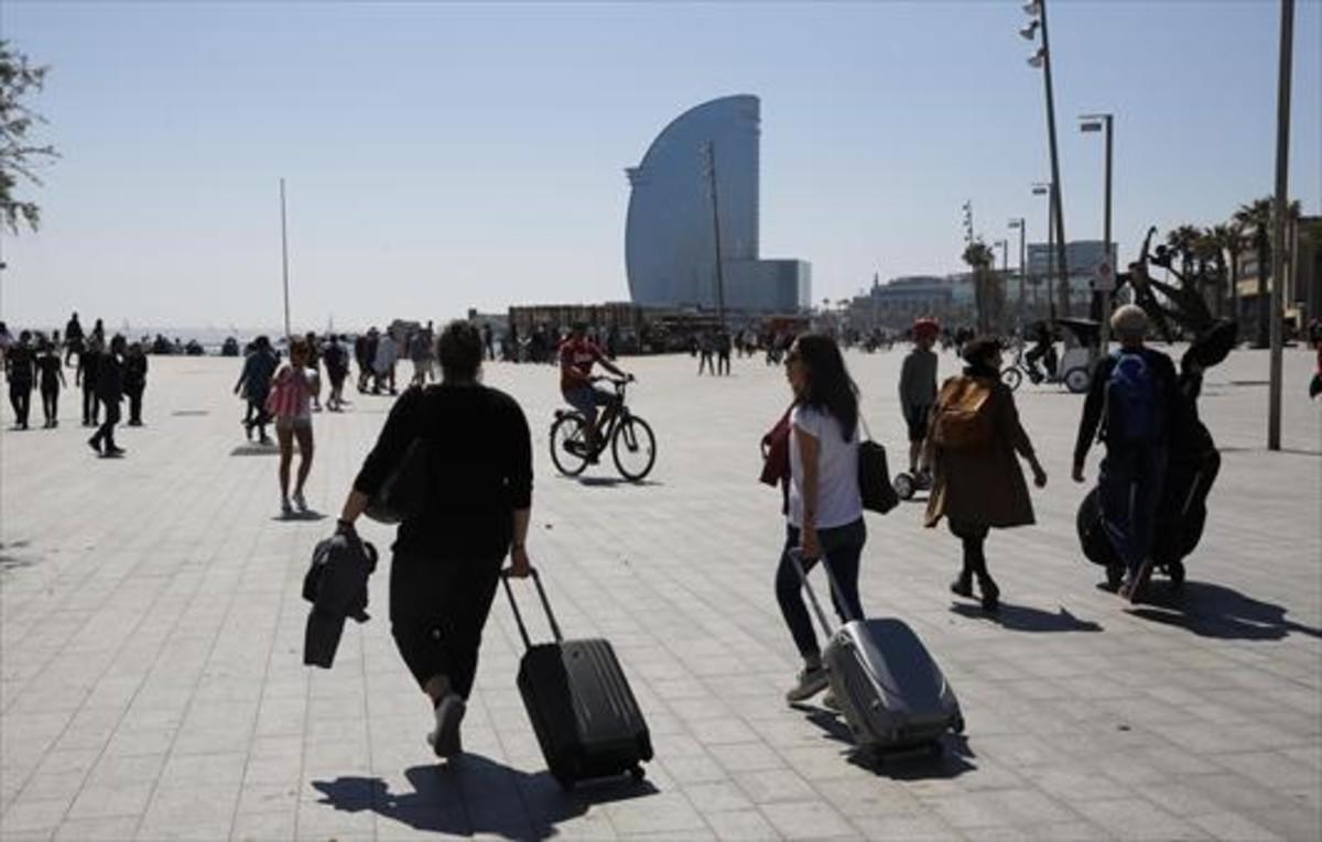 Turistas portan sus equipajes en el barrio de la Barceloneta.