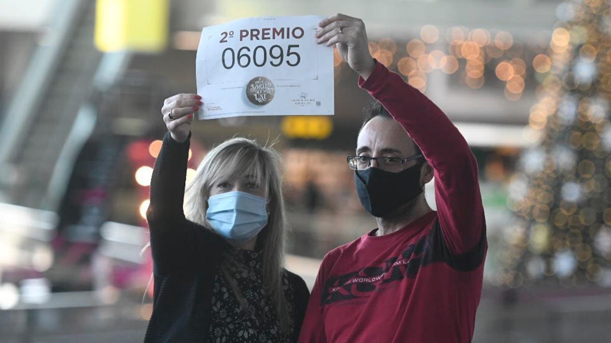 Ana y Miguel Ruiz sostienen el número premiado con el segundo premio de la Lotería de Navidad de las que vendieron dos series en su administración de Badalona.