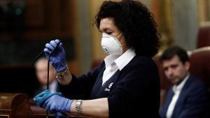 Valentina, ujier en el Congreso,desinfecta el atril tras una intervención de Pedro Sánchez, el 18 de marzo.
