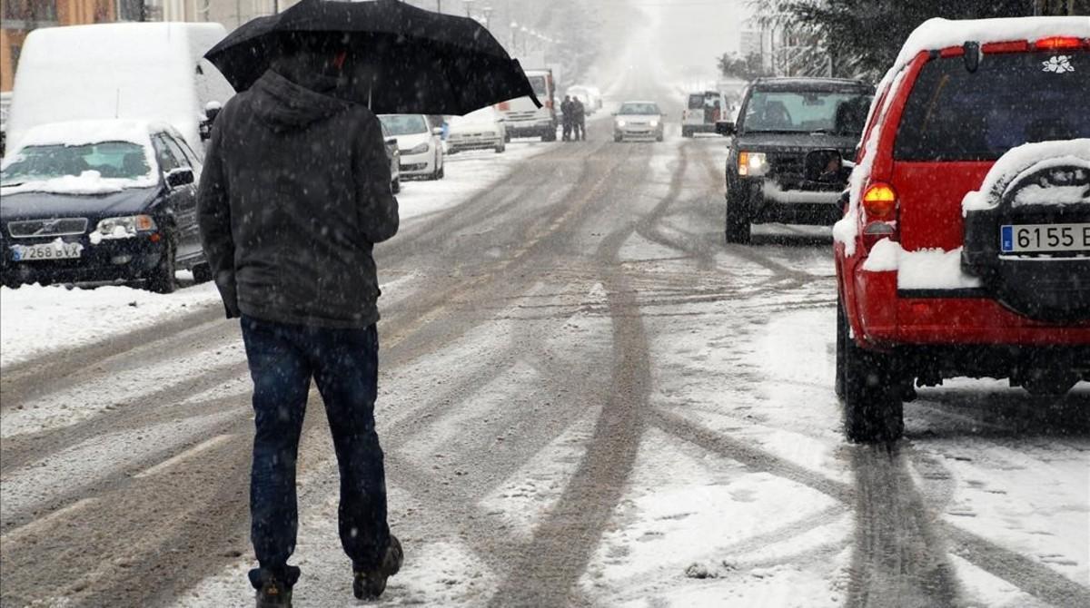Un hombre se protege de la nieve con un paraguas en Esterri d'Àneu (Pallars Sobirà), en una nevada en el 2013.