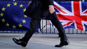 Un hombre camina junto a una bandera de la UE y otra del Reino Unido, en Londres.
