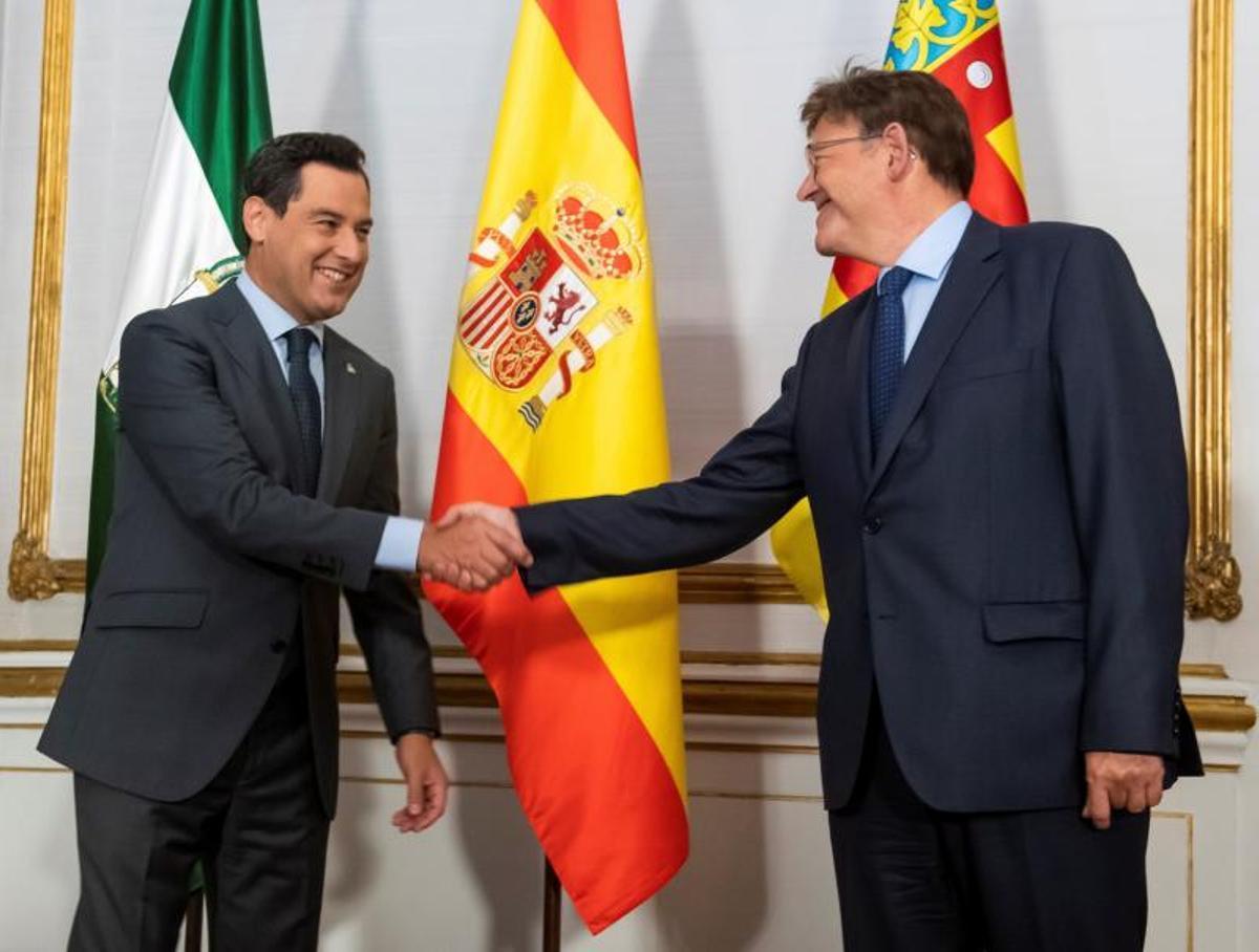 El presidente de la Junta de Andalucía, Juanma Moreno (i), del PP, y el de la Generalitat Valenciana, Ximo Puig (PSOE), se saludan al comienzo de su primera reunión, el pasado 21 de septiembre de 2021 en el palacio de San Telmo, sede del Ejecutivo andaluz, en Sevilla.