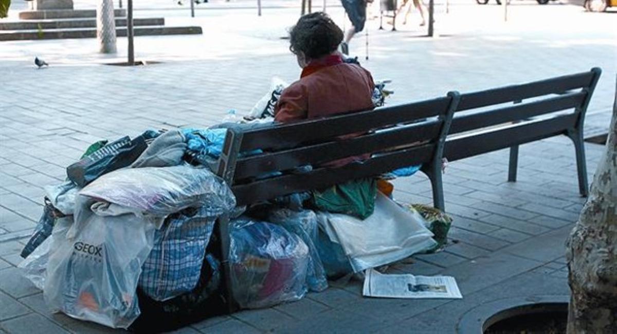 Una mujer sintecho con sus cosas en un banco de la calle de Còrsega.