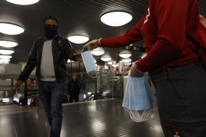 Un miembro de Creu Roja reparte mascarillas en elmetro de Barcelona.