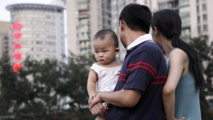 Una pareja observa a unos niños jugando en un parque cargando a su bebe en Shangai (China)