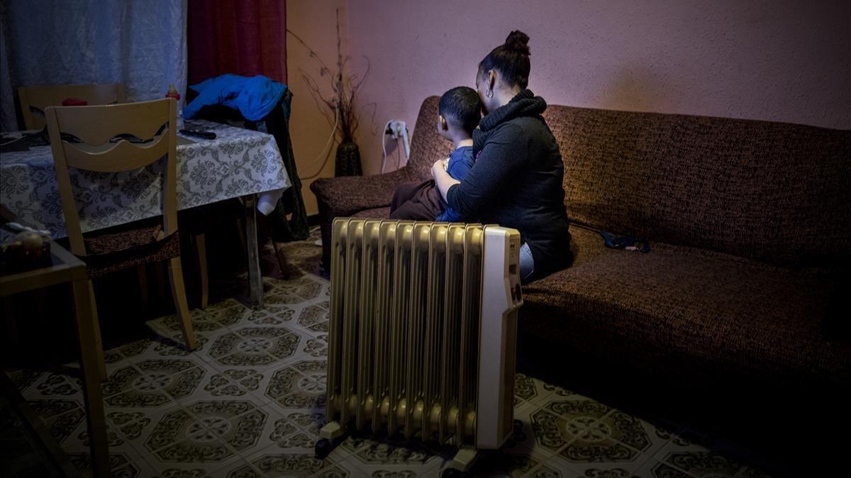 Una dona amb un dels seus fills, víctimes de la pobresa energètica, al seu pisde Barcelona.