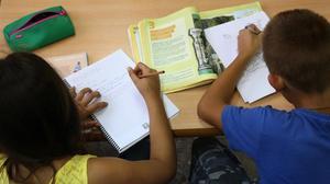 Dos niños de primaria haciendo deberes en su casa, después del colegio.