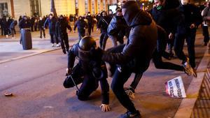 Los manifestantes patean a un agente de policía en Madrid.