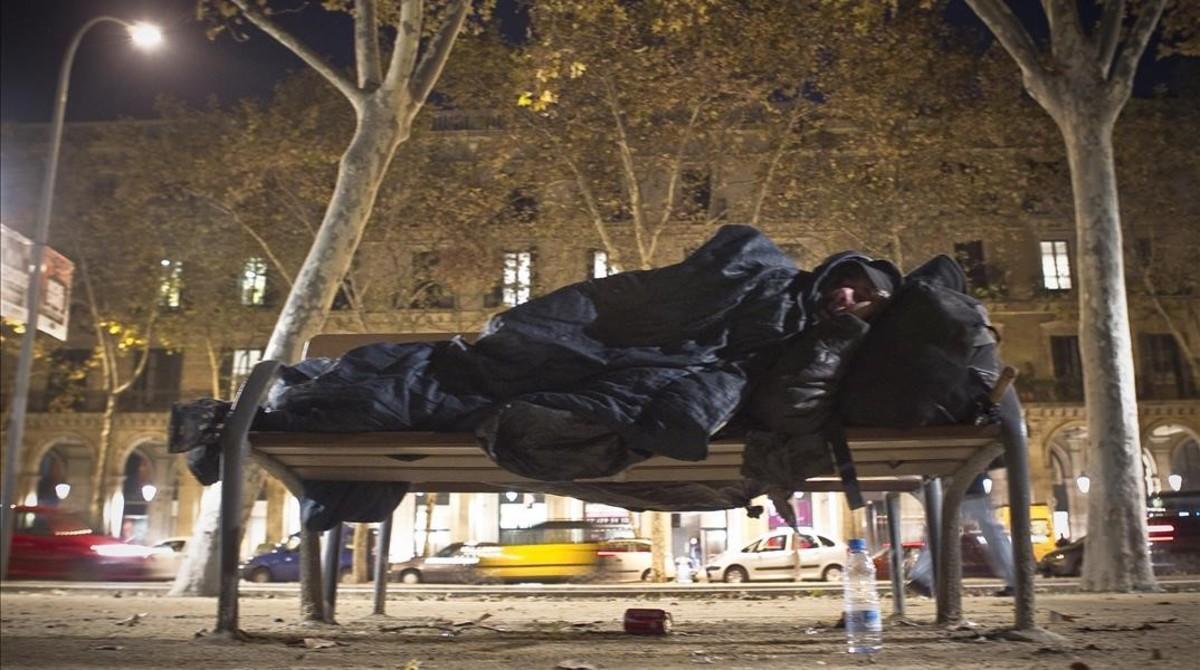 Un sintecho duerme en el parque de la Ciutadella.