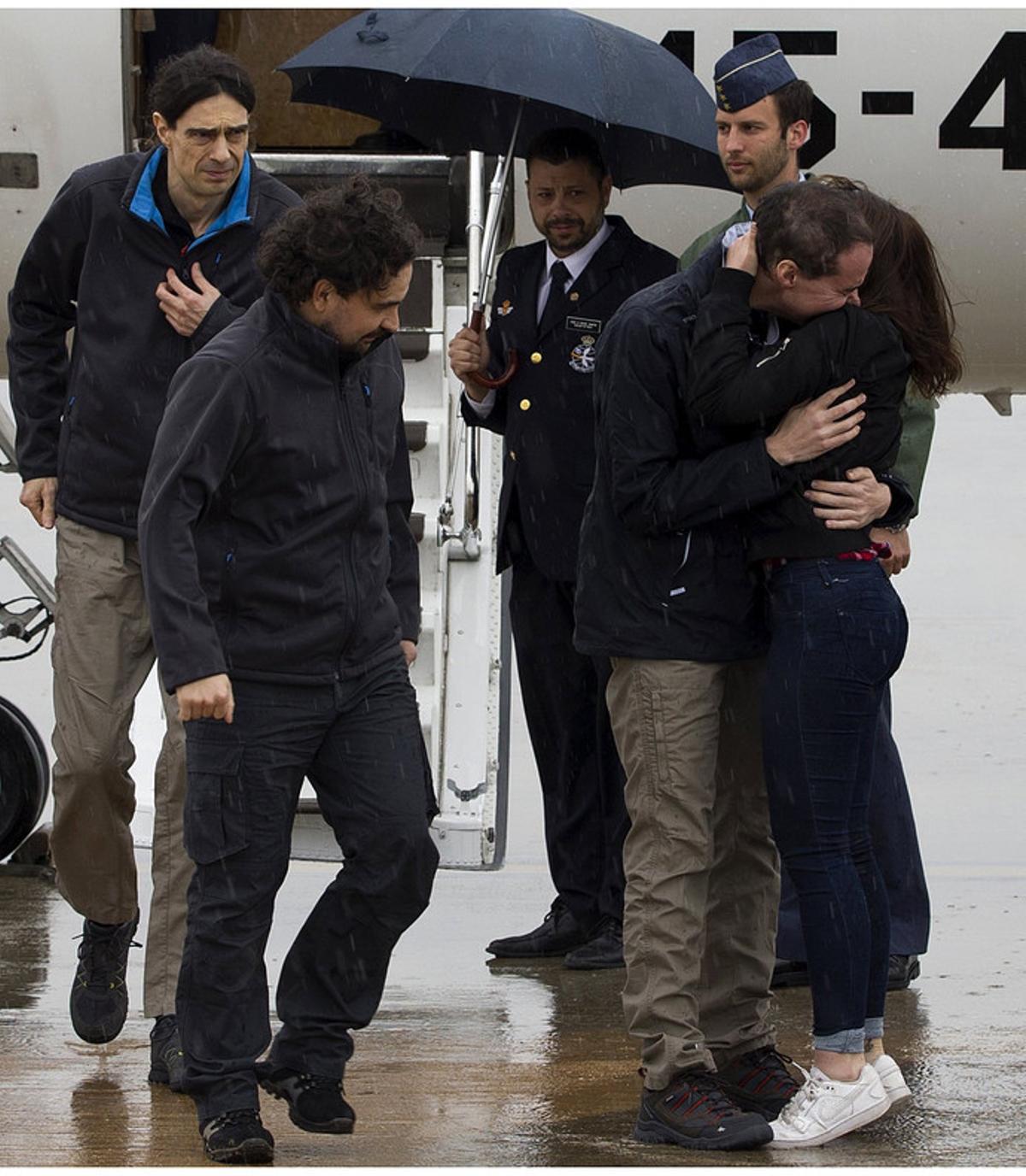 Ángel Satre, en el centro, José Manuel López, a la izquierda, y Antonio Pampliega, a la derecha, abrazado a un familiar.